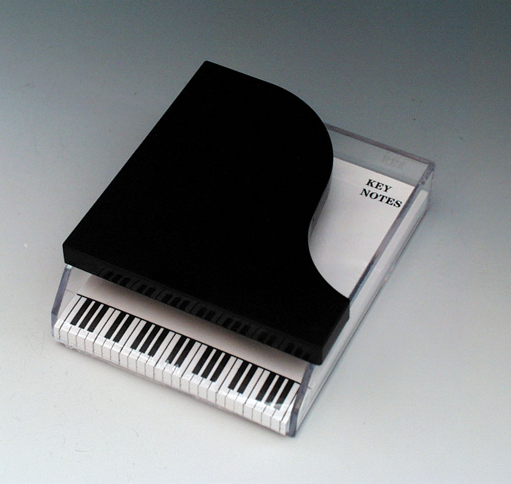 "Acrylic Molded Piano Pad Holder 4.25""W x 5.25""L with a 100-sheet ""Key Note"" pad set. The black piano top is molded onto the clear acrylic base with an inset to accept the ""Key Note"" paper pad set.The paper pad features the imprinted keyboard that sticks o"